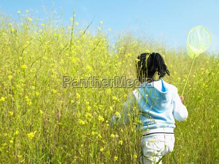 girl carrying net in field of
