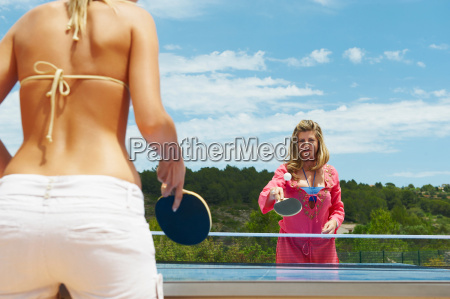 two women playing table tennis outdoors