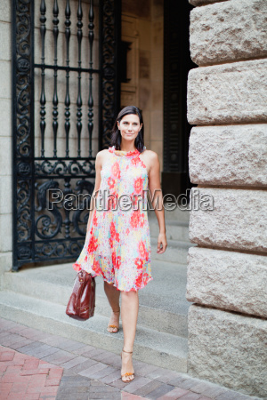 mulher sorridente andando na rua da