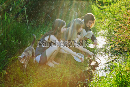 young man and women catching tadpoles