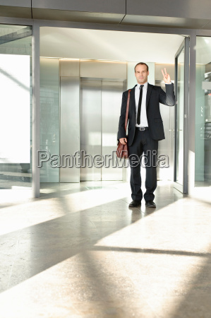 business man making victory gesture