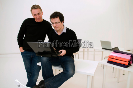 two relaxed business men look at