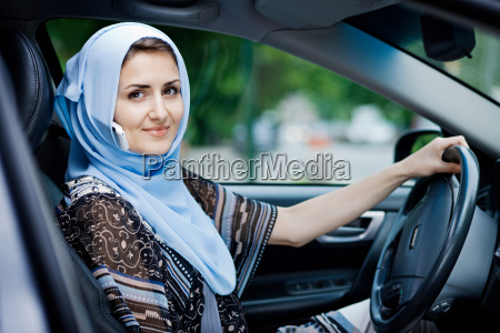 woman in headscarf driving on cell