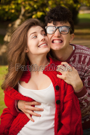 teenage couple making faces in park