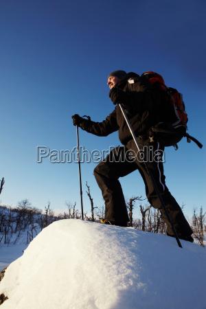 cross country skier walking in snow