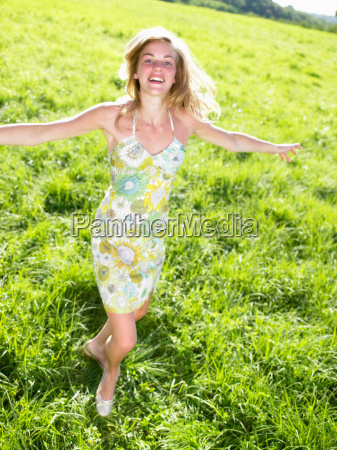 young woman dancing in a green