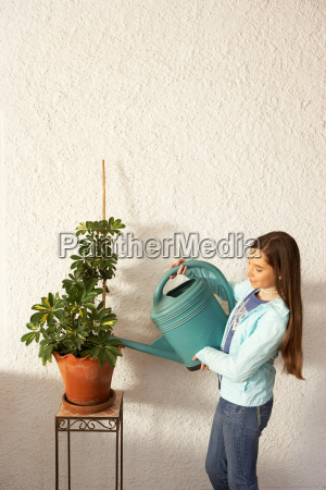 girl watering pot plant