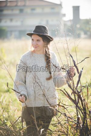 jovem usando chapeu tocando plantas no