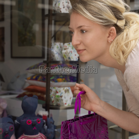 young, woman, looking, at, shop, window - 18428268