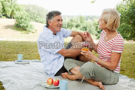 mature couple having picnic in park