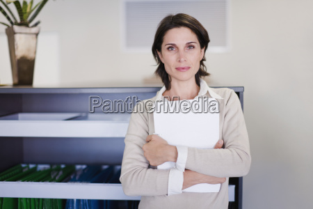 businesswoman holding papers in office