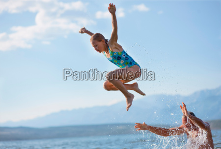 girl jumping from dads shoulders