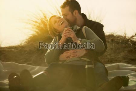 couple on beach cuddling with coffee