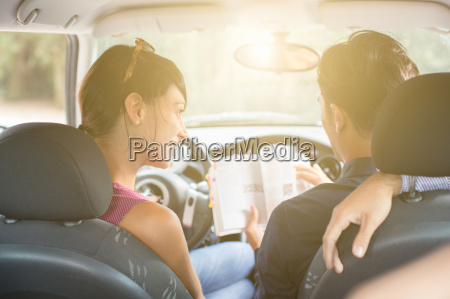 three young adult friends in car