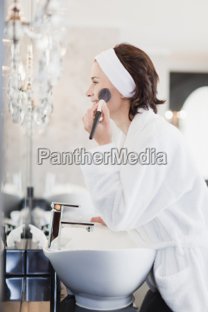 woman in bathrobe applying makeup
