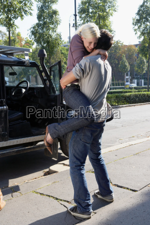 couple embracing by an suv smiling