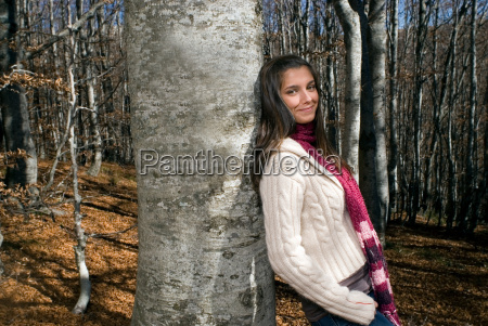 young woman leaning against a tree