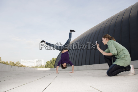 teenage girl photographing young man doing