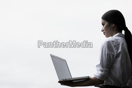 a businesswoman holding a laptop