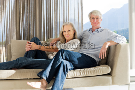 middle aged couple reclining on couch