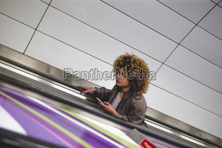 mulher escada rolante trem veiculo transporte