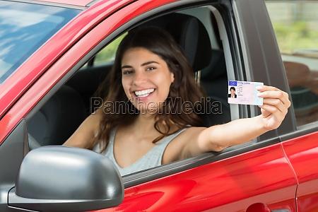 mulher mostrando sua carta de conducao