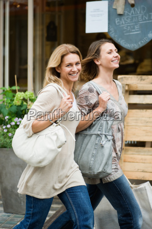 two smiling women walking along the