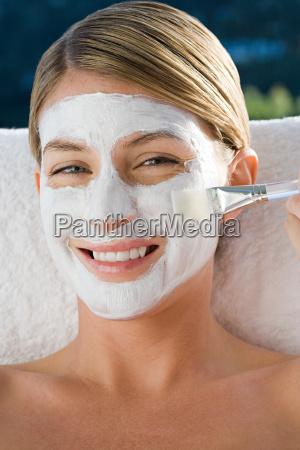 smiling young woman brushing facial mask