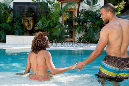 couple holding hands in swimming pool