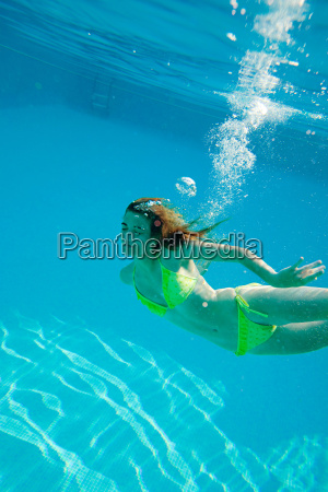 young woman swimming underwater in swimming