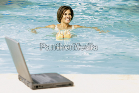 woman in swimming pool with computer