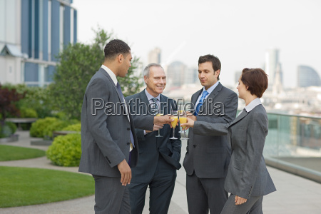 businesspeople outdoors toasting with bucks fizz