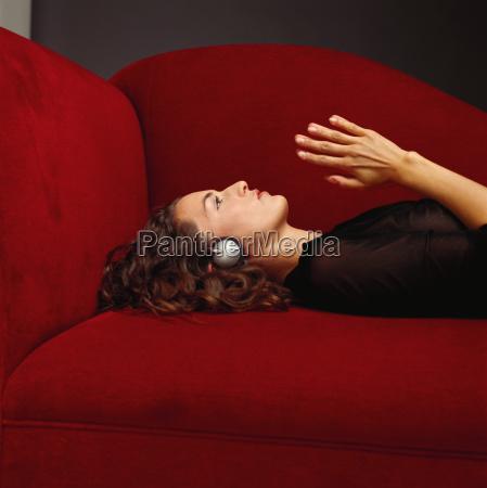 woman wearing headphones on sofa