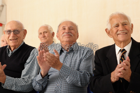 group of elderly men applauding
