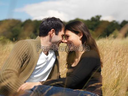 young couple kissing in field
