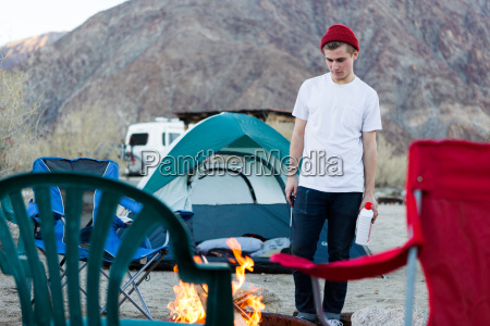 young woman looking down at campfire