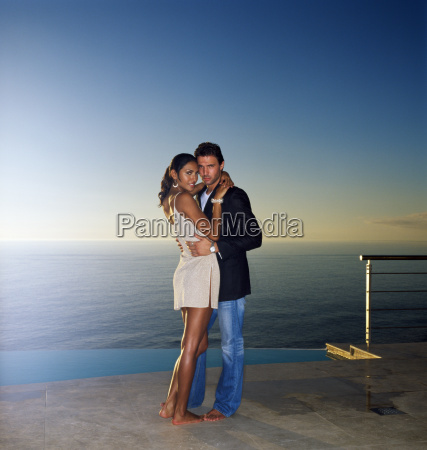 couple hugging by swimming pool