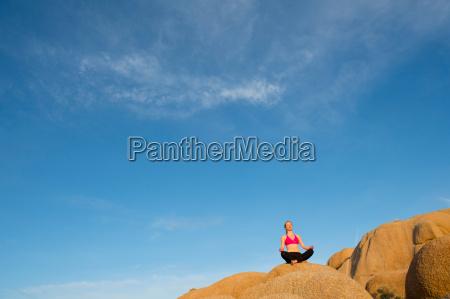 young woman sitting on desert rocks