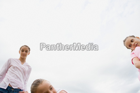 three girls and a cloudy sky