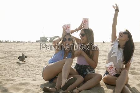 three young women sitting on beach