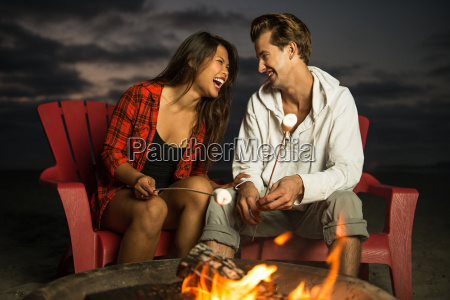 young couple toasting marshmallow in campfire
