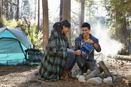 young couple pouring coffee by campfire