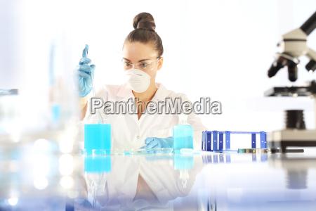o quimico examina a amostra sob