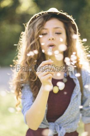 jovem mulher soprando dente de leao