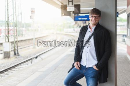 smiling young man waiting at station