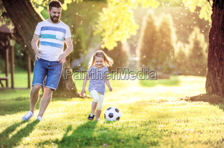 happy little girl playing soccer with