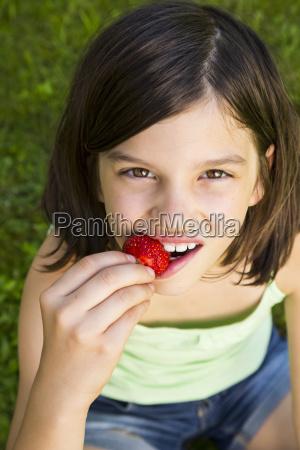 portrait of girl eating strawberry