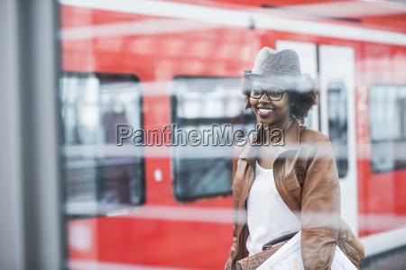 smiling young woman waiting at platform