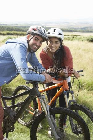 jovem casal pedalando no campo