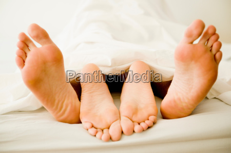 young couples feet under blanket